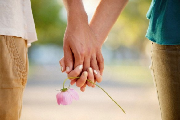 Couple holding hands and flower